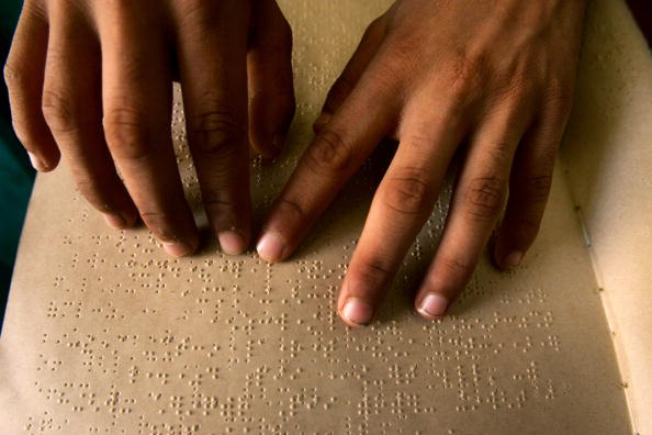 Two hands are reading a braille document in dim lighting