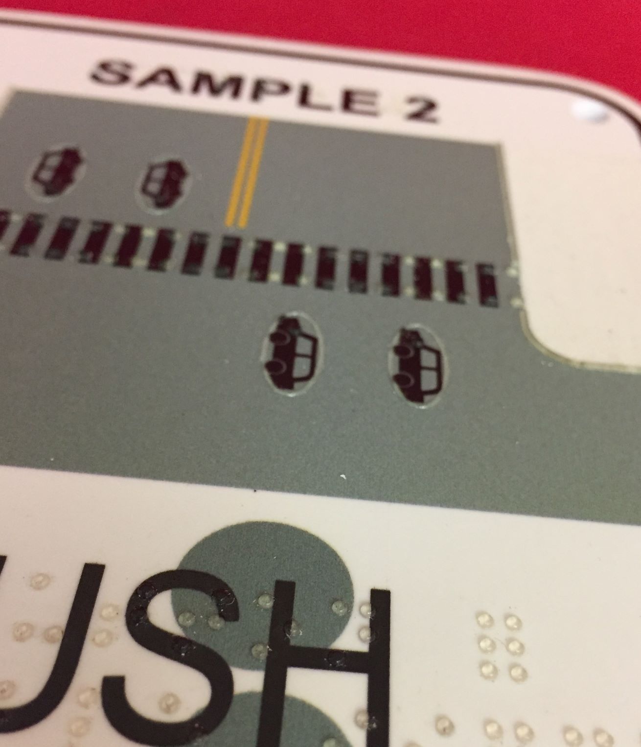 Braille dots and raised tactile graphics on a APS sign