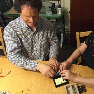 Image of Dr. Miele working with an Arduino board