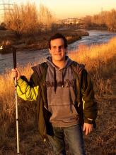 Photo of Christopher Toth with river and grassy banks in background