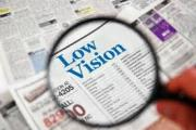 """A magnifying glass is held above a newspaper, focusing on the text """"low vision"""""""